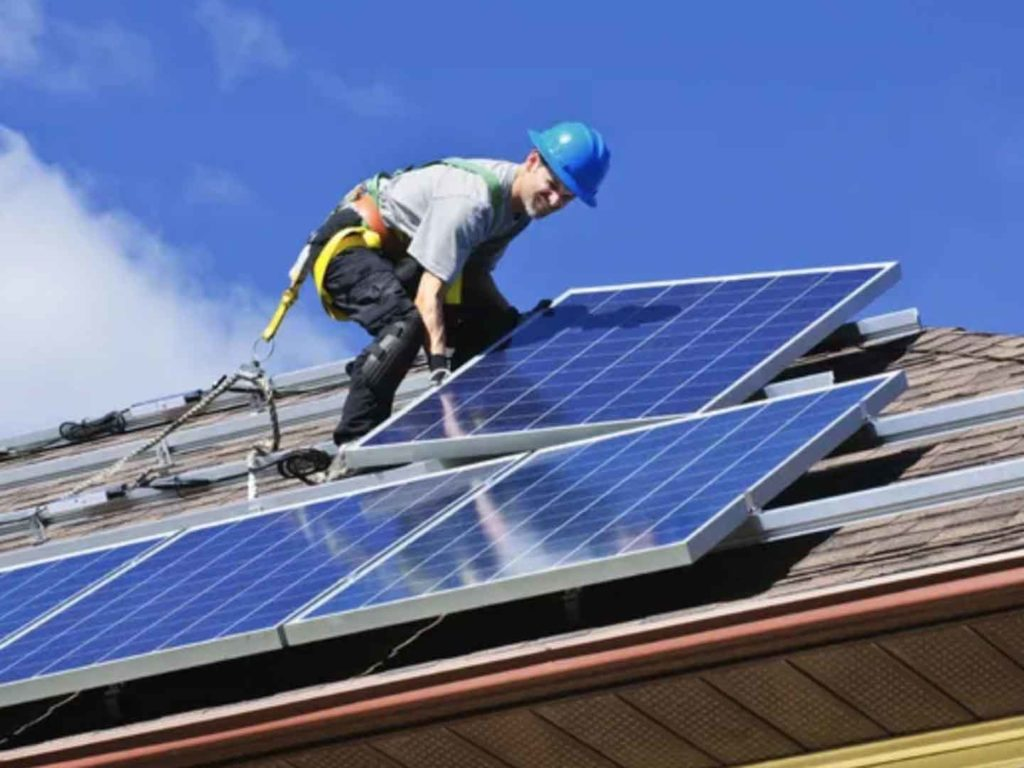 Worker installing solar panels onto a roof