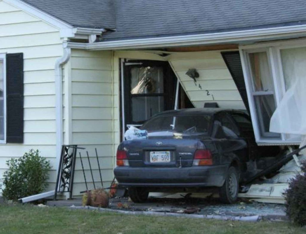 Car that has driven into the front door of a house