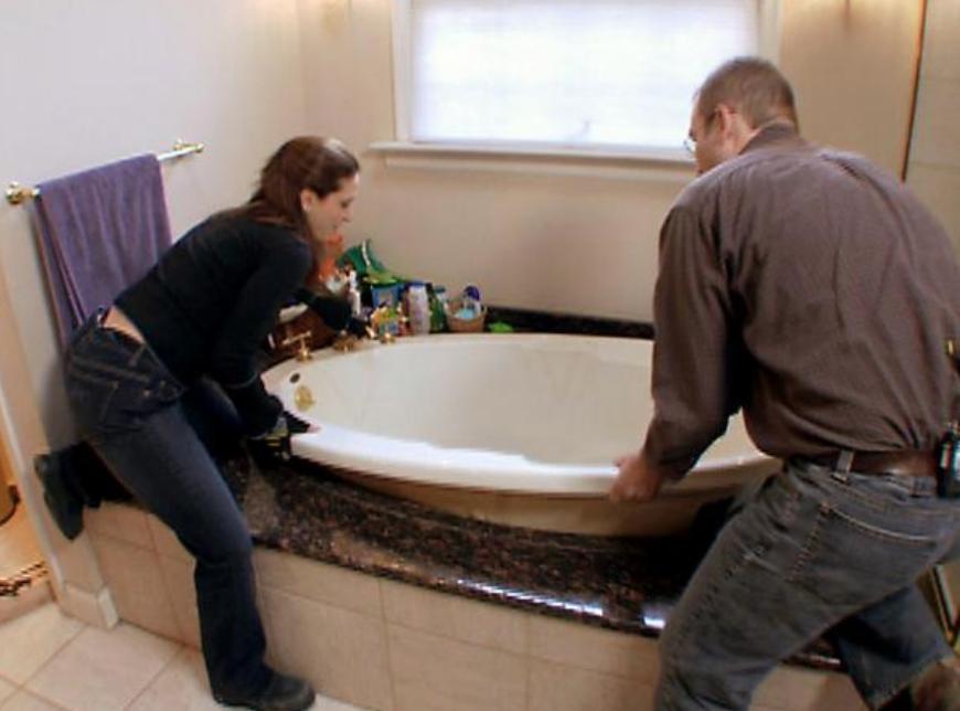 Two contractors installing a bathtub