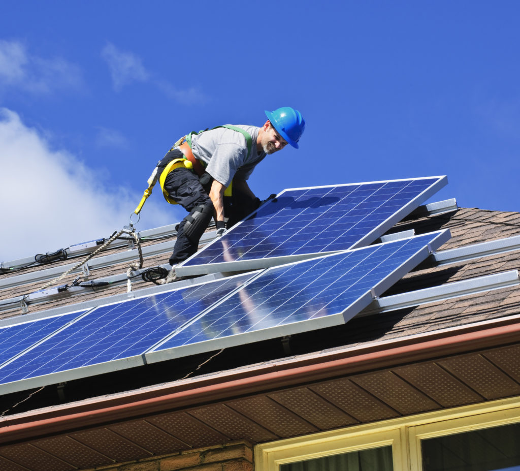 man installing solar panels onto a roof