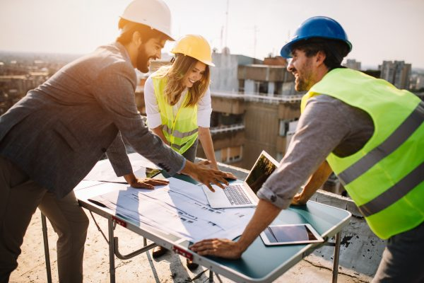 Architects, business manager and engineer meeting project at construction site